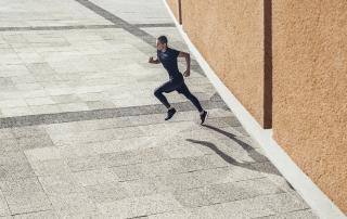 black tights, sneaker, black t-Shirt, running, paved ground, grey, orange walls, orange building