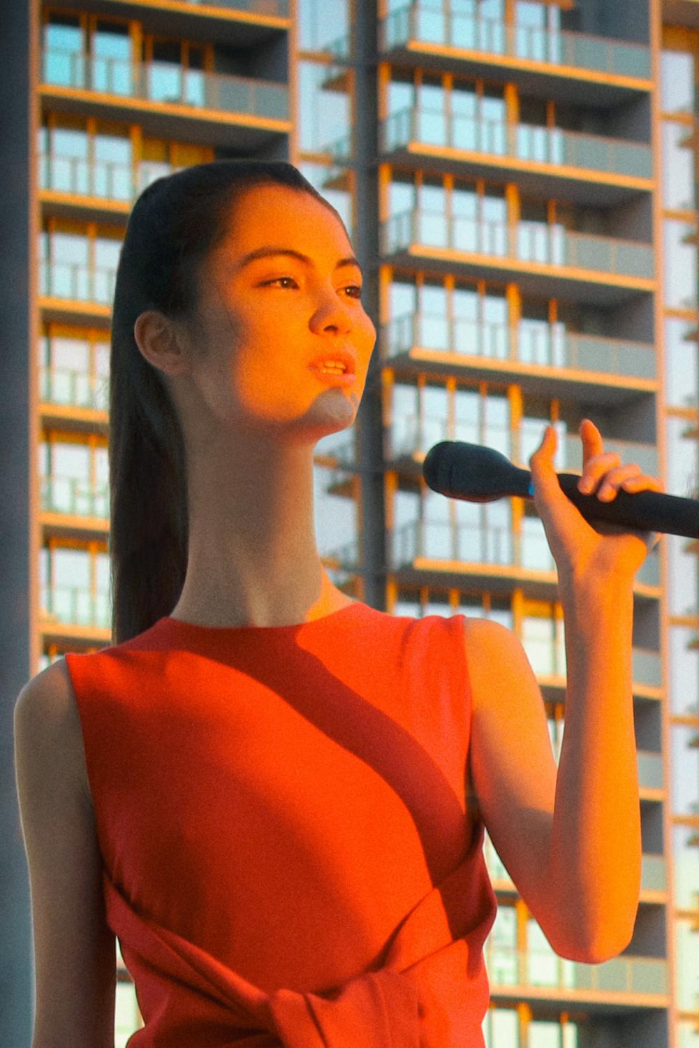 red dress, red top, long neck, black hair, black microphone